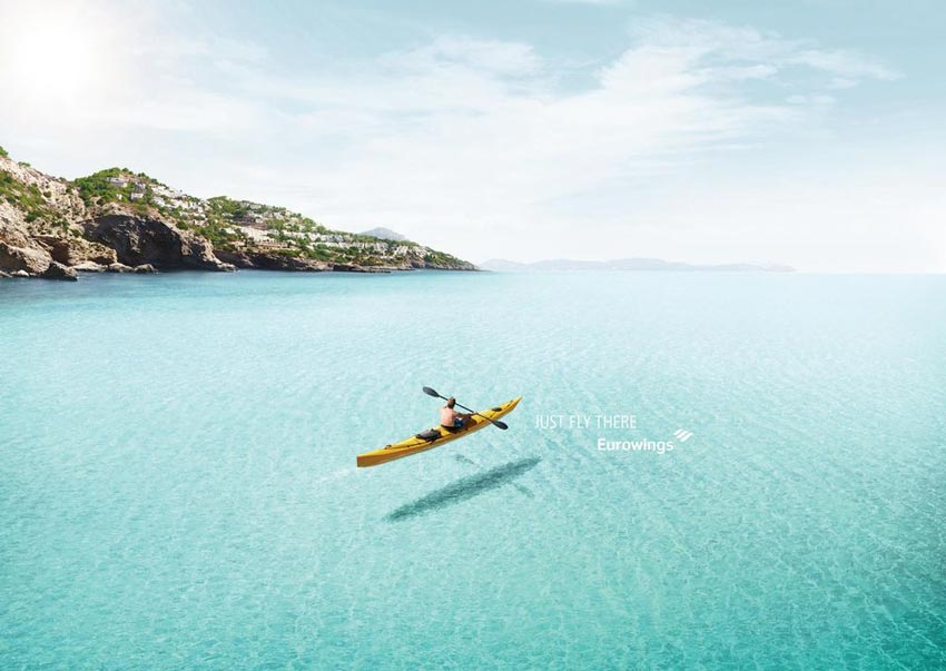 a person on a kayak looks like he is flying because the water is so clear