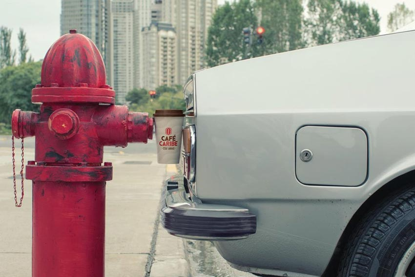 a coffee cup between a car and a hydrant