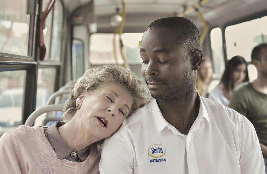 a woman sleeping on a Serta employee's shoulder